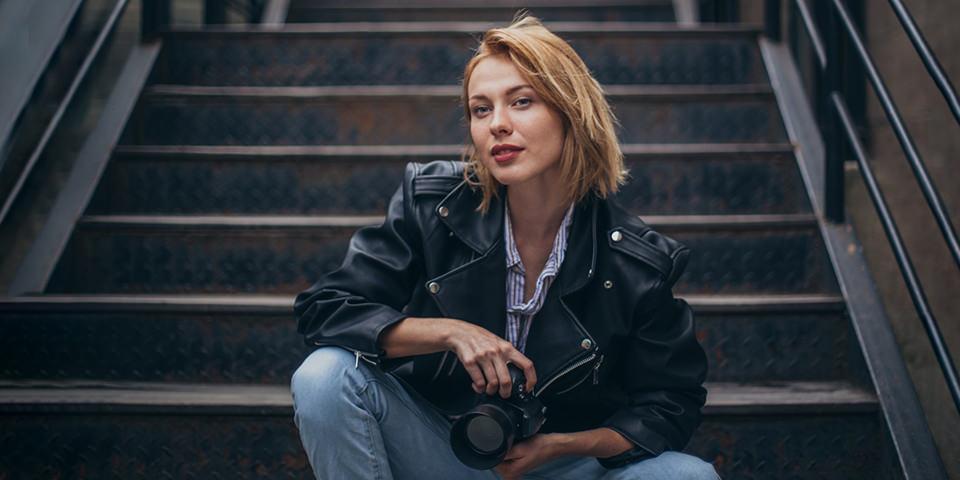 Frau sitzt mit Kamera auf einer Treppe
