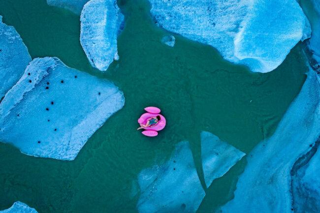 Frau im Badeanzug auf einer pinken Flamingo-Luftmatratze zwischen Eisschollen