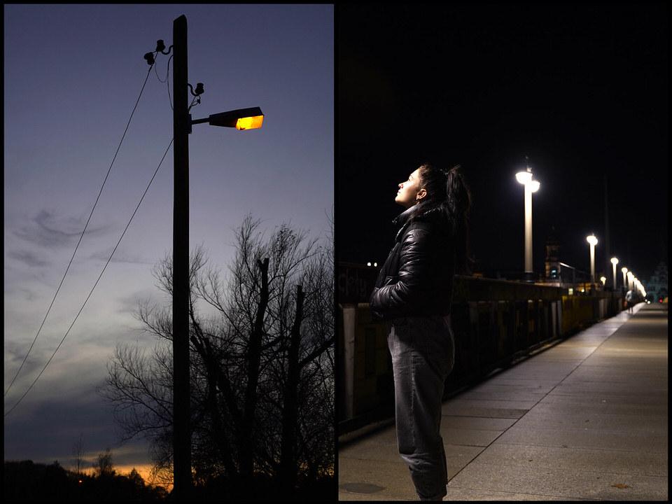 Frau an einem Bahnsteig schaut auf eine Laterne
