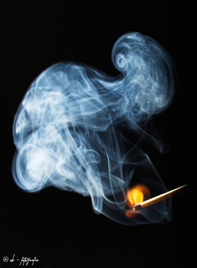 Streichholz mit Feuer und Rauch