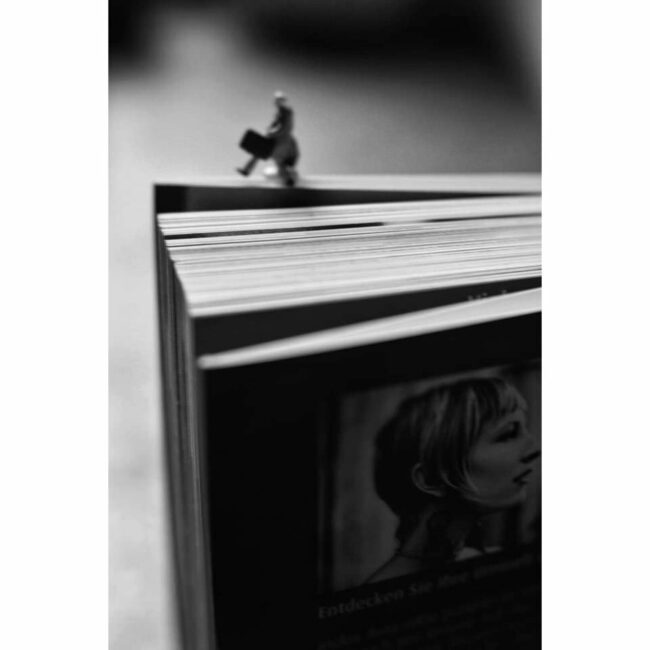 Kleine Person läuft auf einem Buch