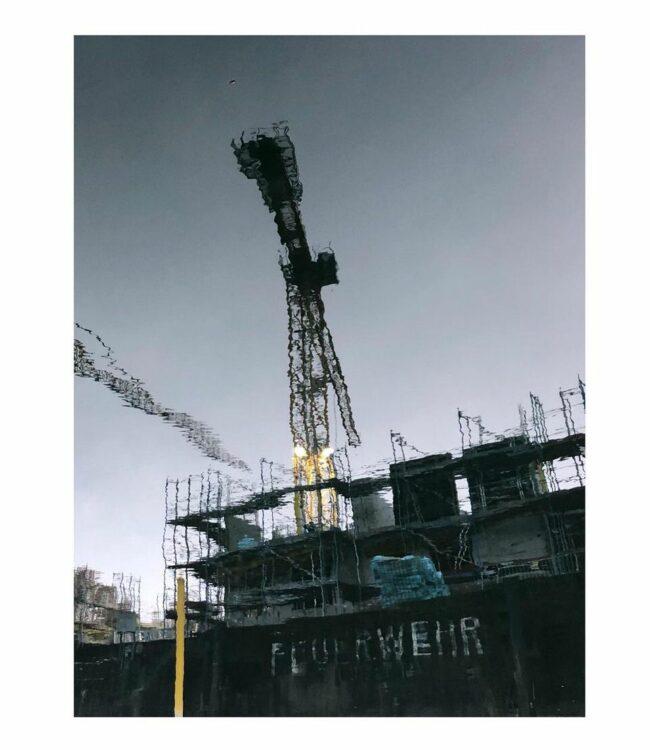 Baustelle durch eine Pfütze fotografiert