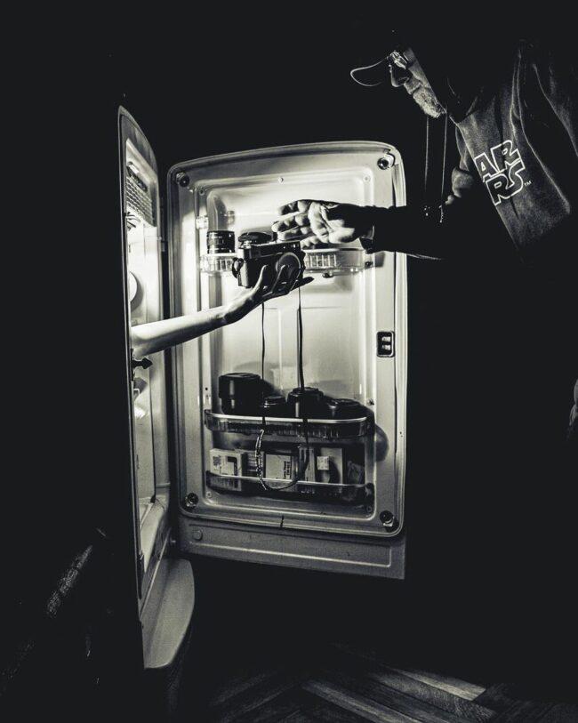 Hand reicht etwas aus einem Kühlschrank