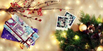 weihnachtliches Flatlay mit Pflanzen, Geschenken und Polaroids