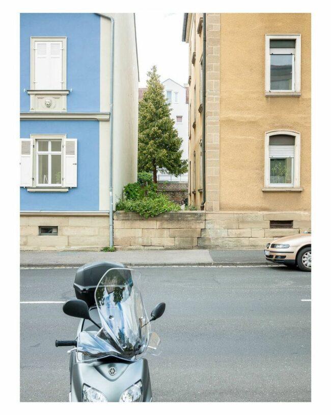 Straße mit angeschnittenem Auto und Moped