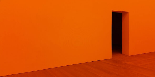 Oranger Raum mit dunklem Eingang