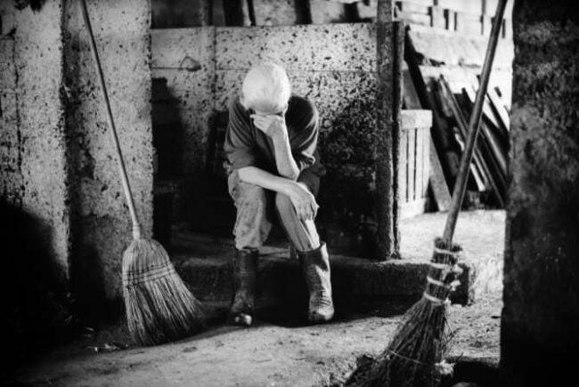 Trauernde Frau in einem Stall zwischen zwei Besen