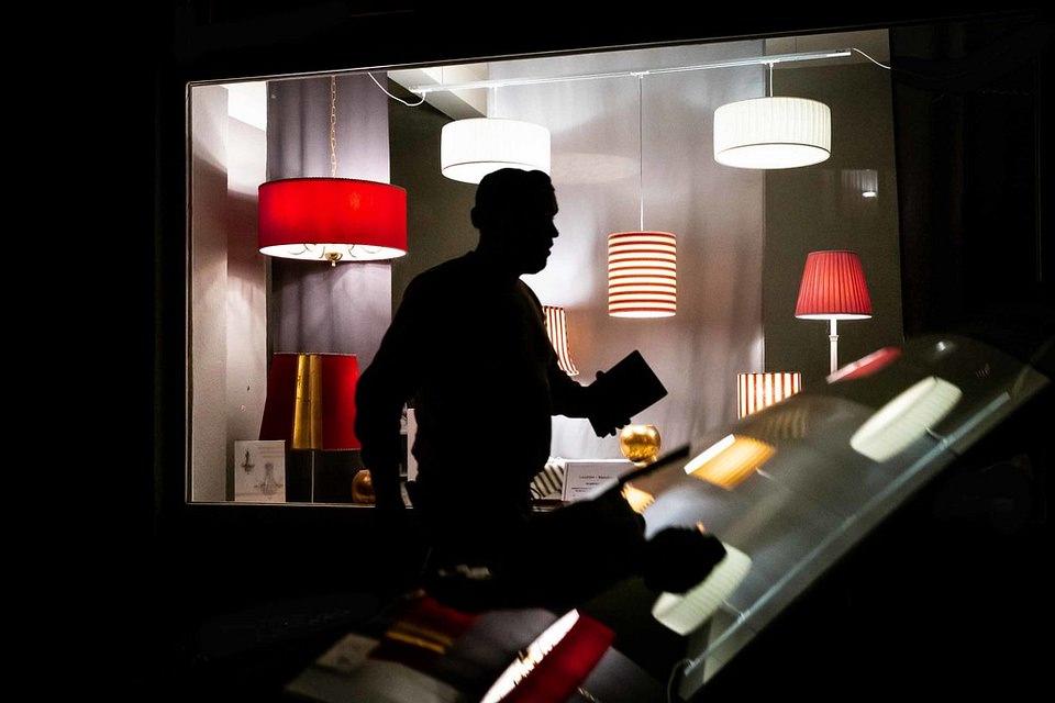 Silhouette vor Schaufenster mit Lampen