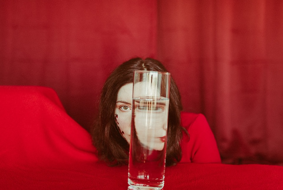 Portrait mit Wasserglas in roter Umgebung