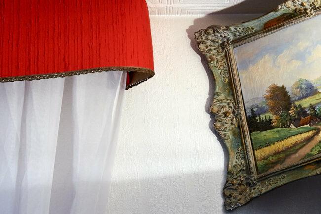 Ausschnitt: Bilderrahmen und Vorhang vor Tapete
