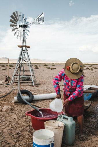 Person füllt Flüssigkeit in einen Behälter vor einem Windrad