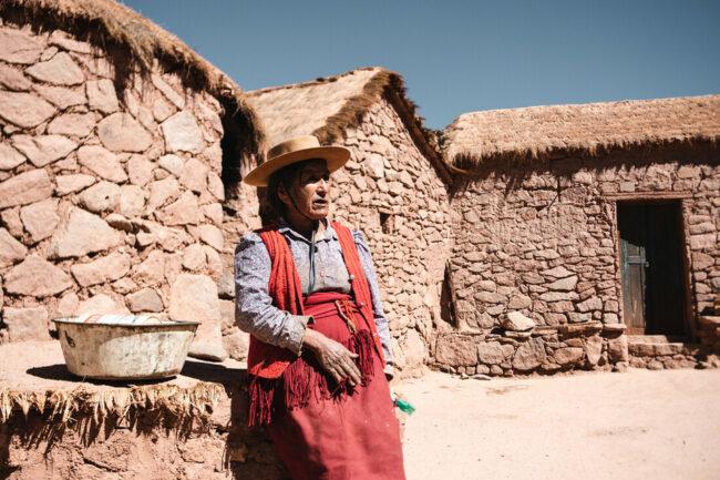 Frau an einem Steinhaus
