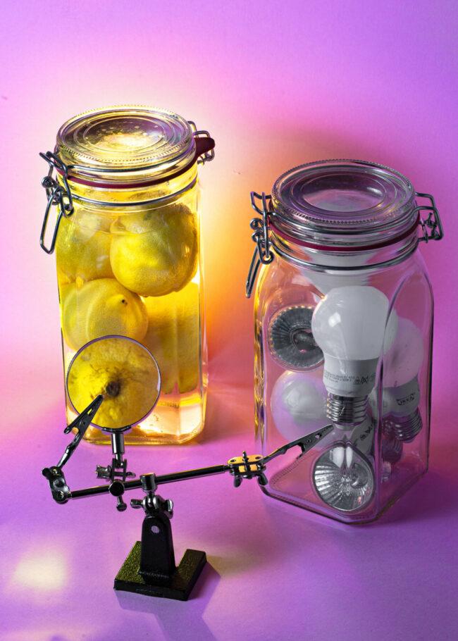Zwei Einmachgläser, eins gefüllt mit Zitronen, das andere mit Glühbirnen