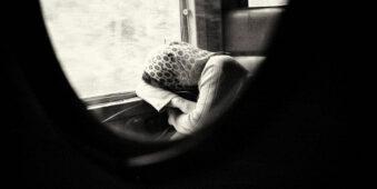 Schlafende Person im Zug mit Tuch bedeckt