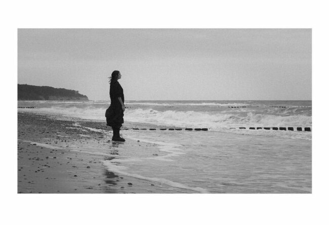Person steht am Meer