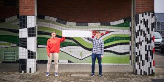 zwei Personen halten einen Banner vor einer bunten Wand hoch