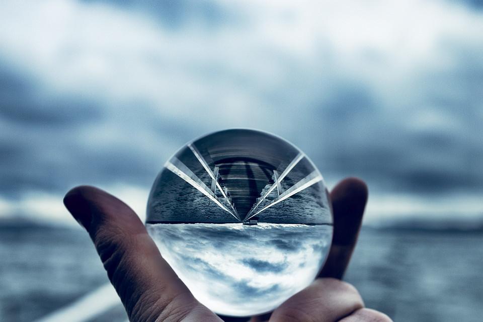 Hand mit Glaskugel vor Wasserlandschaft