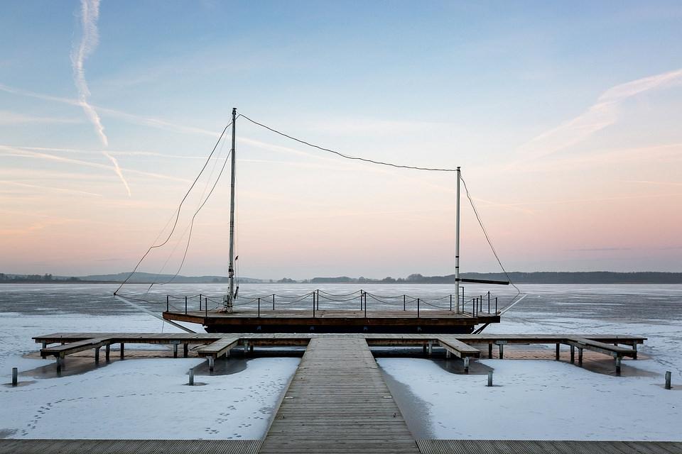 Schiff liegt am Steg eines gefrorenen Gewässers