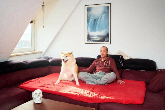 Ein Mann und ein Hund sitzen auf einer Luftmatratze in einem Zimmer