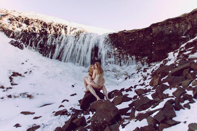 ein nacktes Paar vor einem vereisten Wasserfall