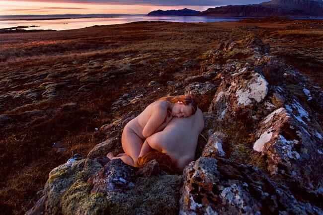 Zwei nackte Menschen liegen auf Steinen in der Landschaft