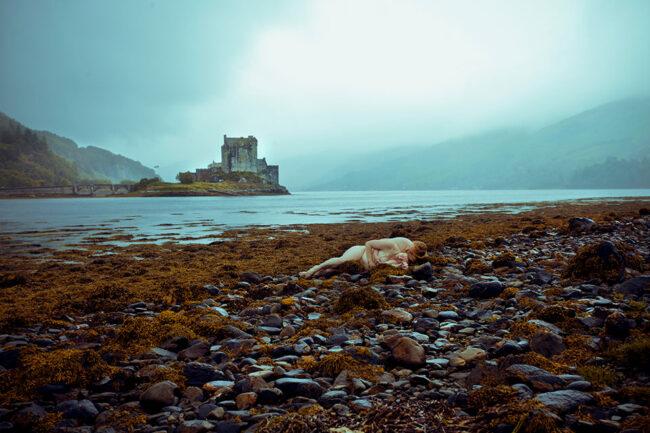 Zwei nackte Menschen liegen an einem Ufer vor einer Burg