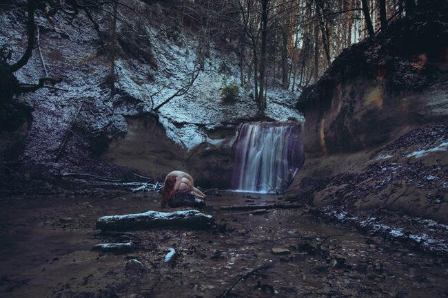 Zwei anckte Körper liegen aneinander vor einem Wasserfall