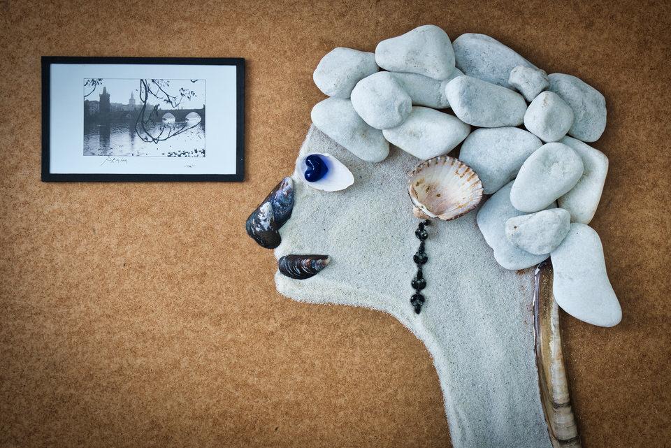 Kopf aus Sand und Steinen schaut auf ein Bild