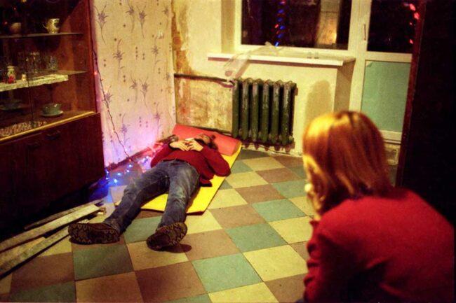 Eine Person liegt auf einer Matte auf dem Boden, eine andere sieht ihr dabei zu