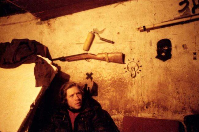 Person lehnt an einer Wand, an der eine Waffe hängt