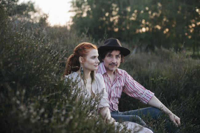zwei Personen sitzen in hohem Gras