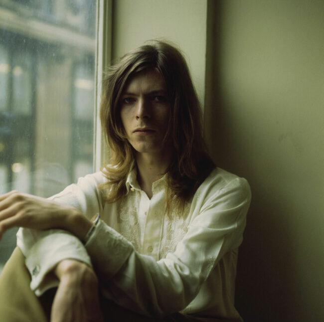 David Bowie posiert an einem Fenster sitzend