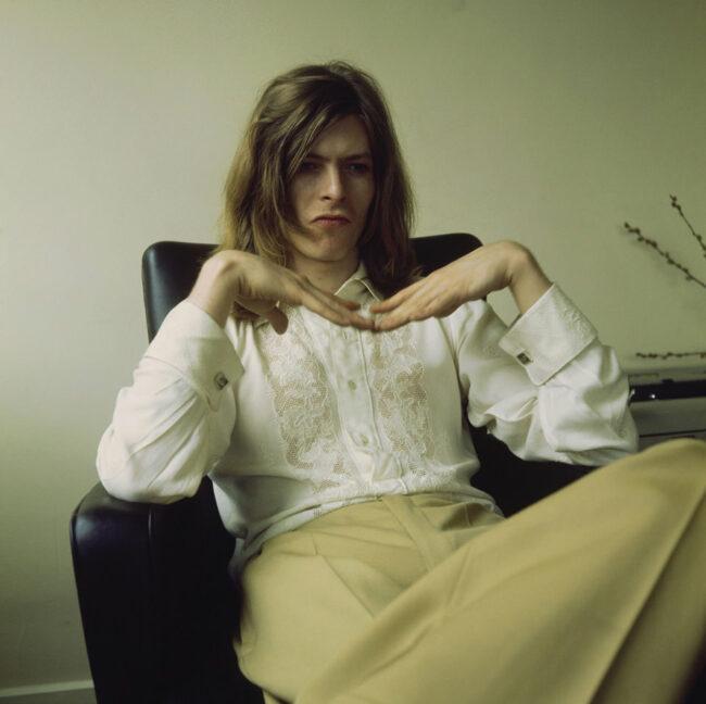 David Bowie posiert auf einem Sessel sitzend