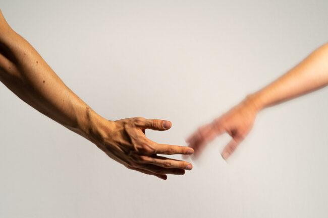 Zwei Hände greifen einander, eine ist unscharf