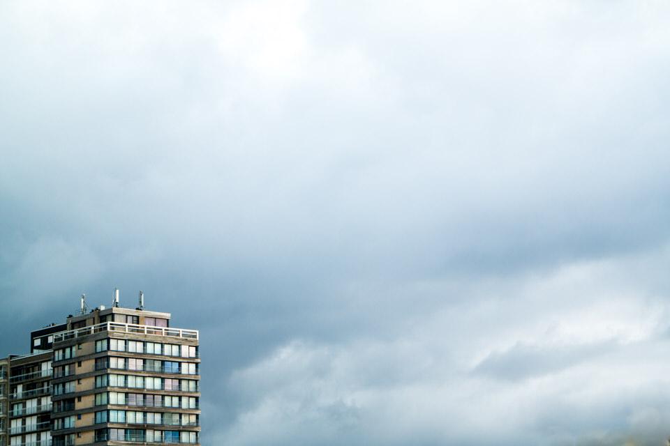 Hochhaus klein in der Ecke vor weitem Himmel