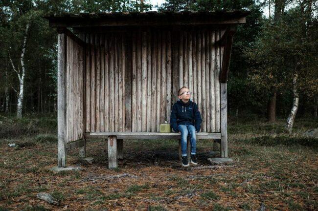 Eine Junge sitzt in einem Wartehäusschen