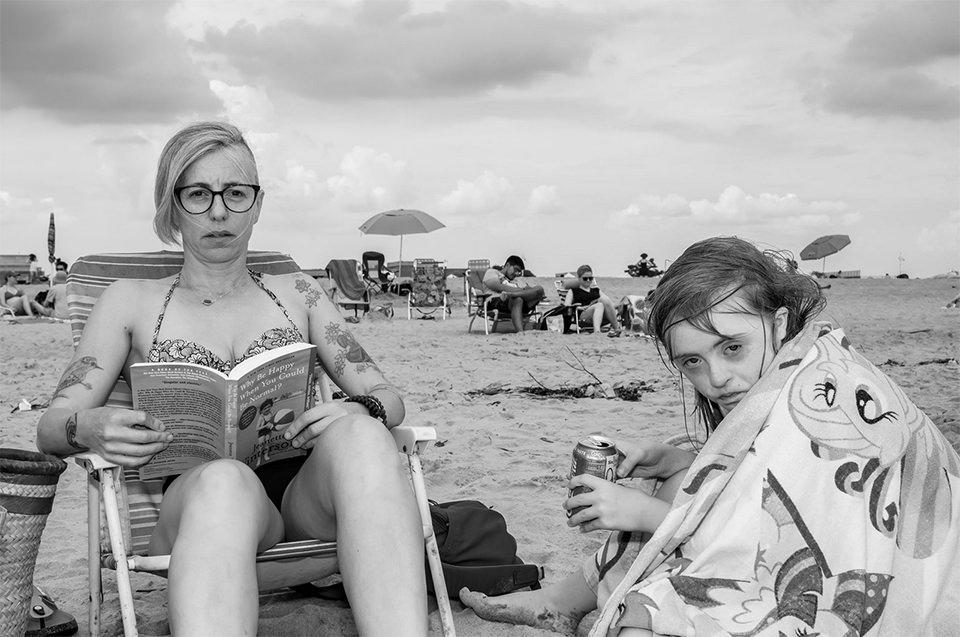 Frau und Kind am Strand und schauen genau in die Kamera