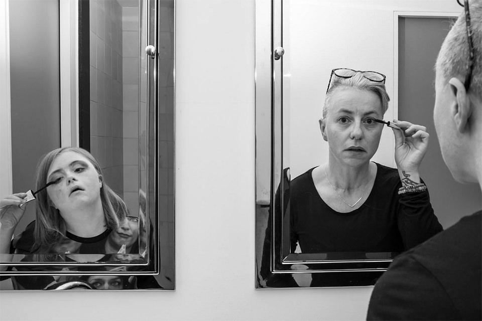 Frau und Kind schminken sich und sehen die betrachtende Person durch den Spiegel an