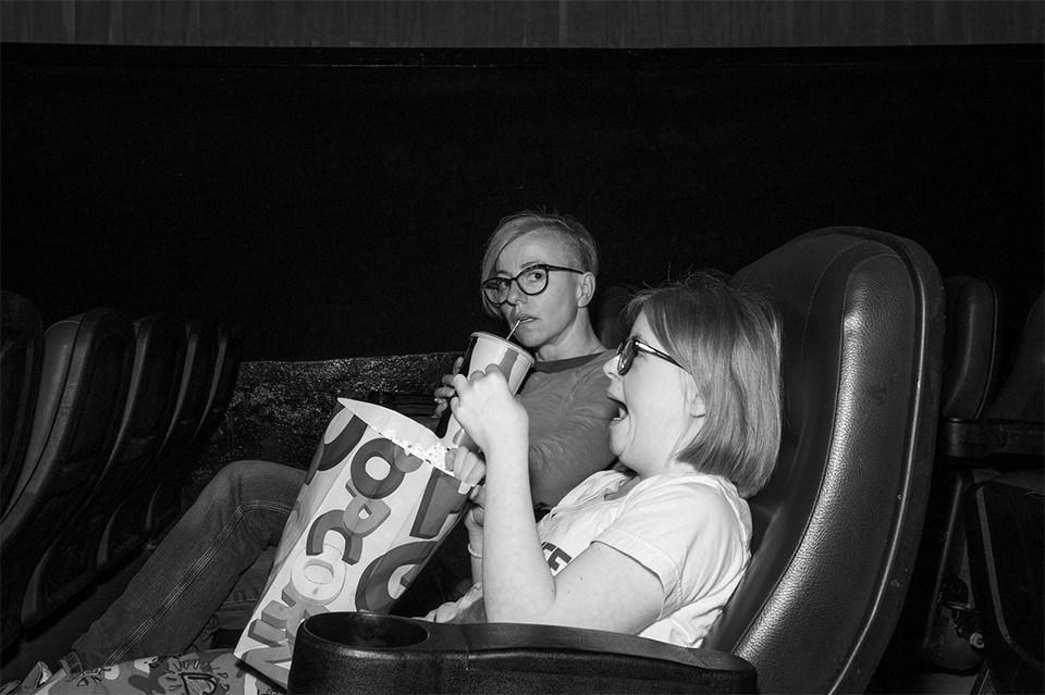 Frau und Kind im Kino, die Frau schaut genau in die Kamera