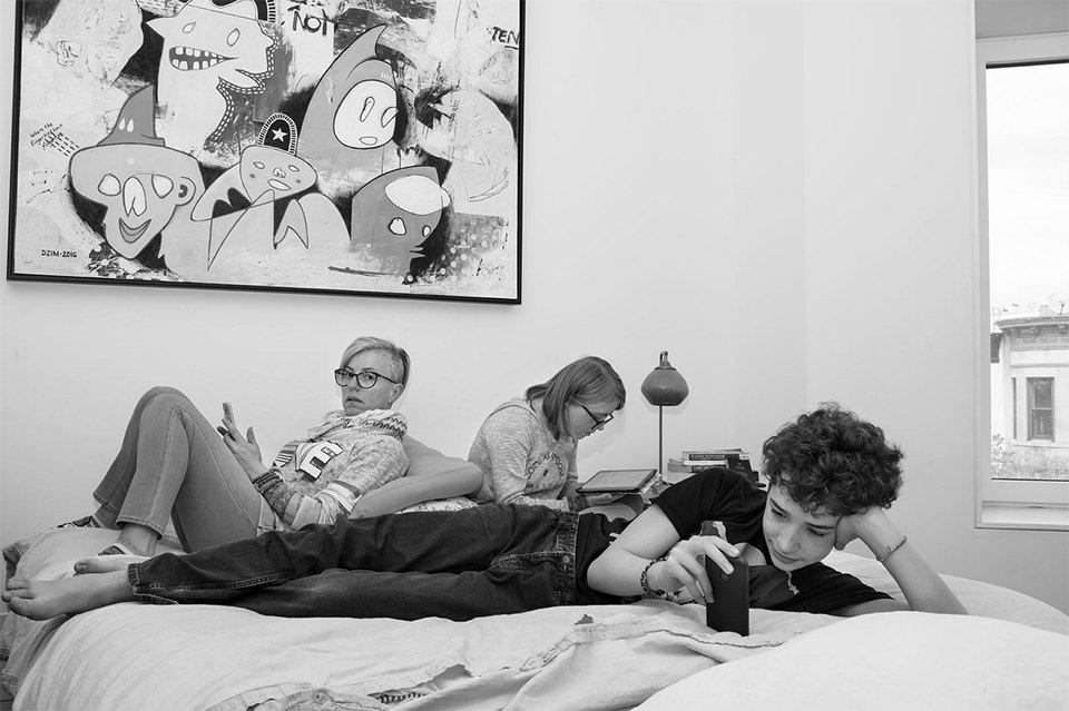 Frau und zwei Kinder liegen auf einem Bett