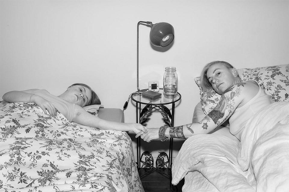 Frau und Kind liegen in getrennten Betten und halten sich an den Händen