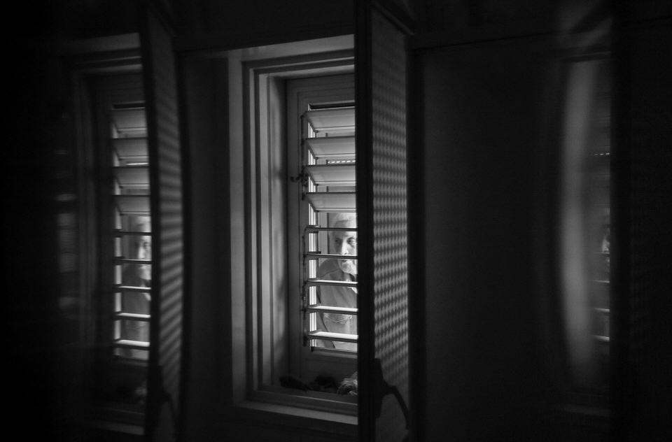 Zwei Personen sehen durch zwei Fenster in ein Zimmer
