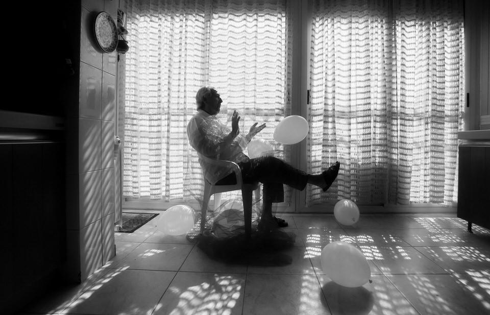 Mann sitzt auf einem Stuhl mit Luftballons