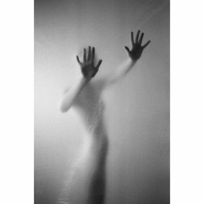 Person hinter einer hängenden Folie hält die Hände dagegen