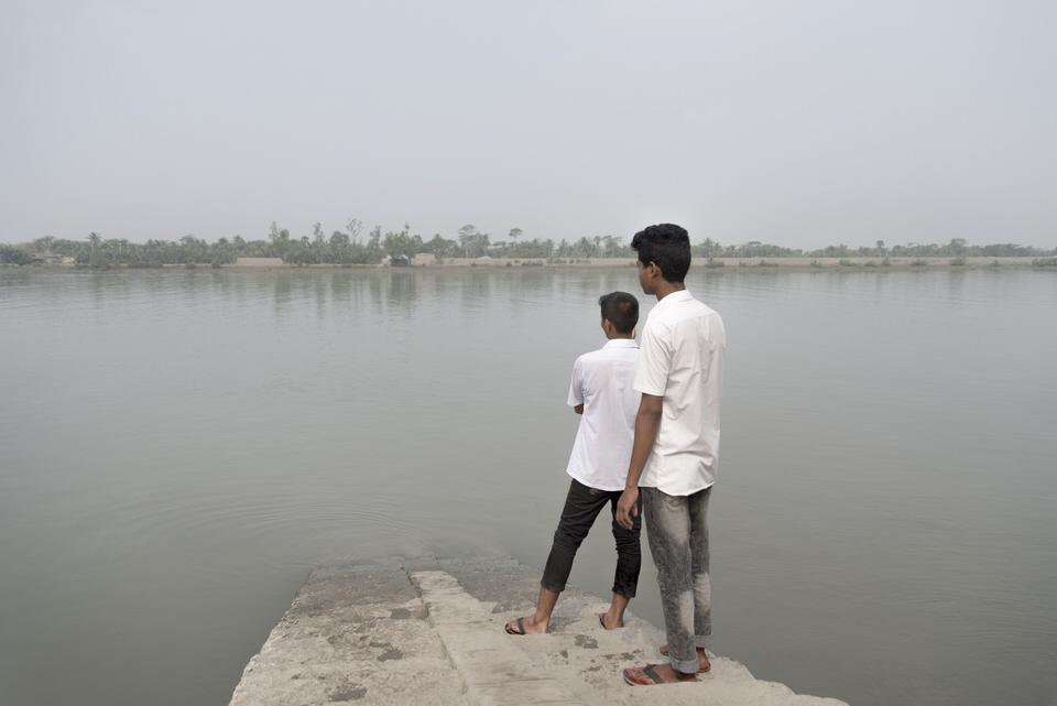 Zwei Personen stehen an einem Wasser und schauen ans andere Ufer