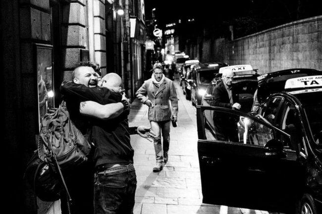Straßenszene. Ein Spaziegänger und zwei Männner, die sich umarmen
