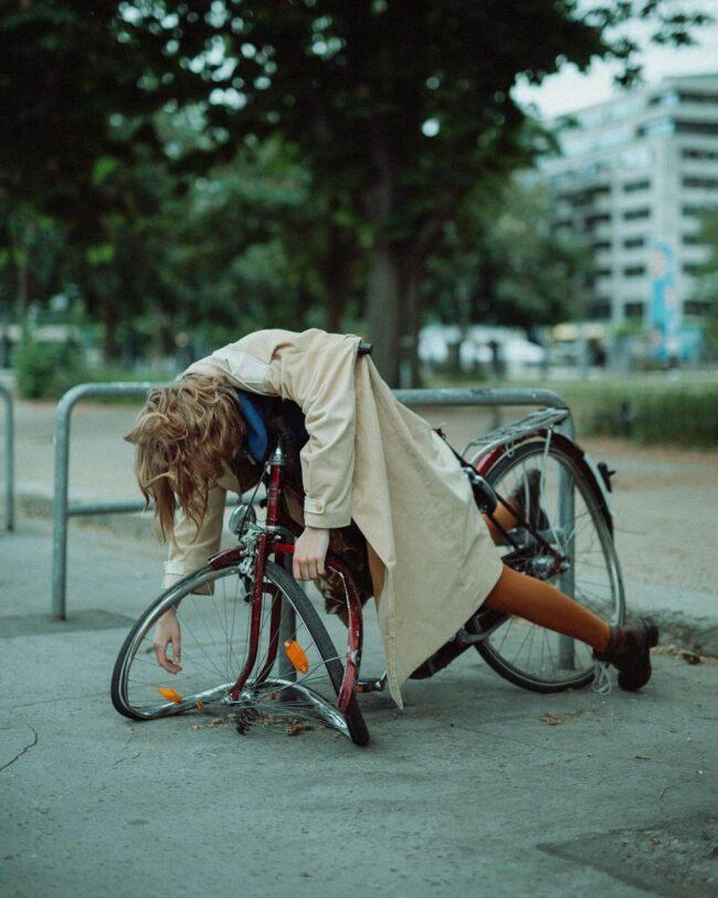 Frau liegt auf einem kaputten Rad