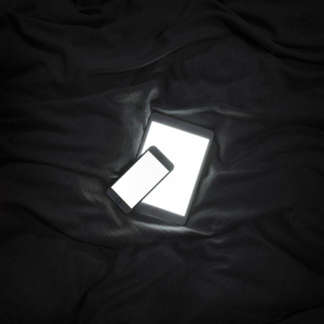 Tablet und Handy leuchten hell auf einem Laken