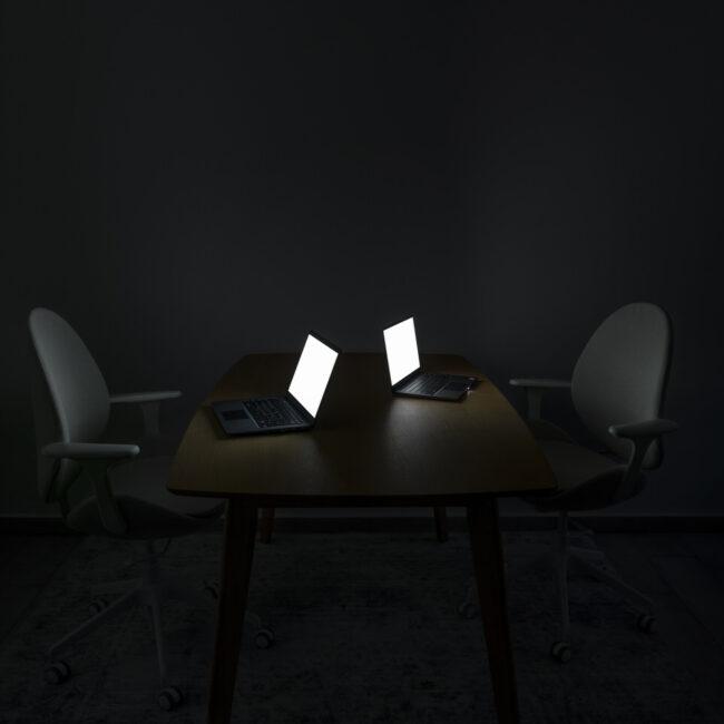 Zwei Schreibtische mit hellleuchtenden Monitoren
