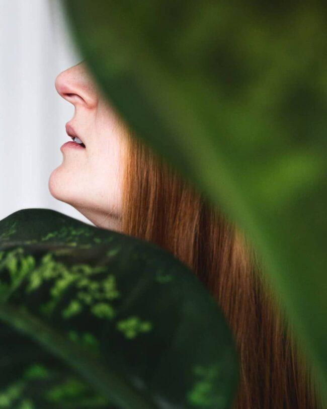 Person hinter grünen Blättern